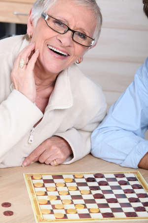checkers: An old laughing lady playing checkers with somebody. Stock Photo