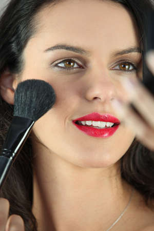 maquillage: Young woman putting some make-up on