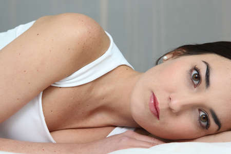 ennui: Bored brunette laying in bed Stock Photo