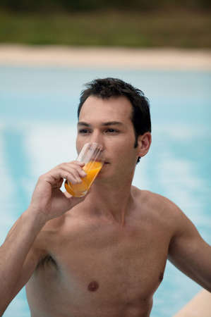 Man drinking orange juice in the pool photo