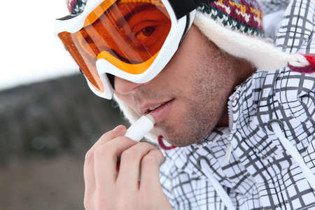 young skier putting cold cream lip stick on his lips Stock Photo - 11947882