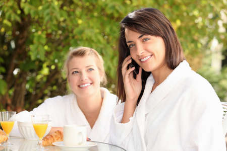 Woman on a mobile phone at breakfast photo