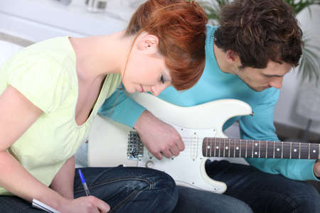 selections: a woman writing and her boyfriend playing guitar Stock Photo