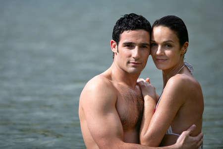 pareja apasionada: Pareja que se abraza mientras se bañaba en el mar