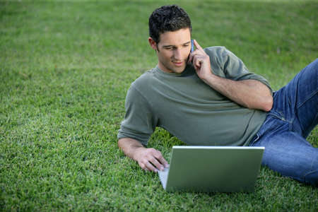 Relaxed man using phone and computer laid on the grass photo