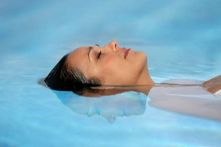 Woman with her eyes closed in a swimming pool photo