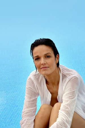 Brunette wearing wet shirt sat by pool photo