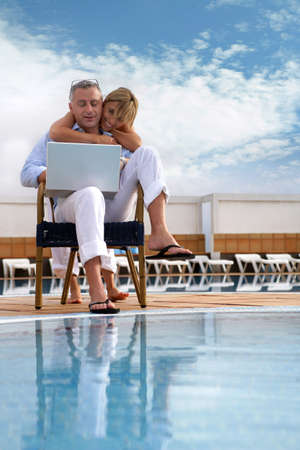 Couple looking at a laptop by a pool photo