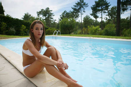Young woman lounging by the pool photo