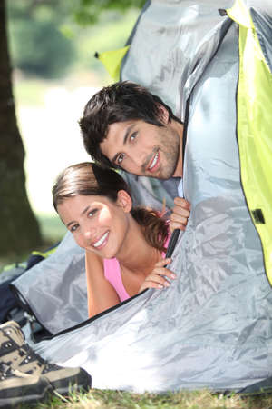 Young couple sticking their heads out of a tent door Stock Photo - 11947318