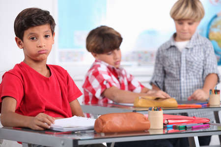 social worker: little boy sighing in a classroom Stock Photo