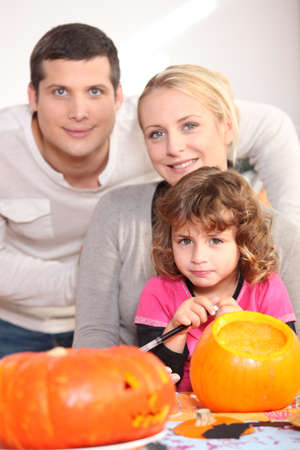 8 years: Family carving pumpkins together Stock Photo