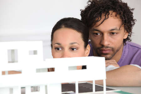 Couple looking at model housing photo