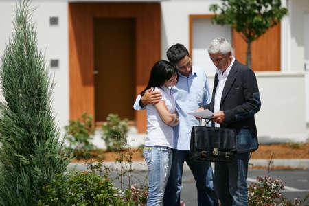 agente: Agente immobiliare e giovane coppia leggendo un giornale