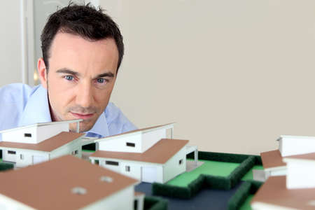 Architect looking at model housing photo