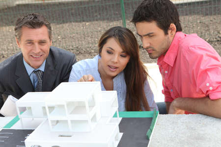 new development: Agent and young couple with a model of a new development Stock Photo