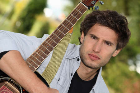 tightly: Man tightly holding his guitar