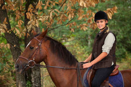 riding helmet: Mujer joven montado en un caballo por el bosque Foto de archivo