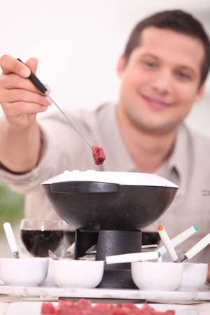 30 years old man: 30 years old man eating meat fondue Stock Photo