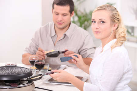 Couple eating raclette photo