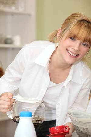 submissive: fair-haired girl pouring coffee Stock Photo