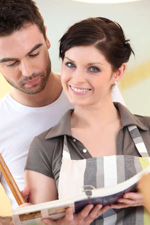 Couple looking at a cookbook Stock Photo - 11946781