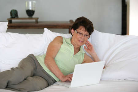 silver surfer: Mature woman using her laptop on a sofa