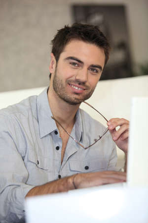 Man with laptop removing glasses photo