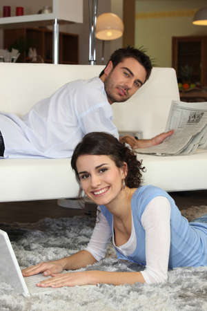 evening newspaper: Couple relaxing in their living room