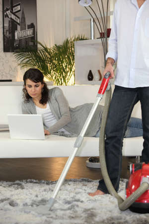 Man vacuuming and woman laid with laptop photo
