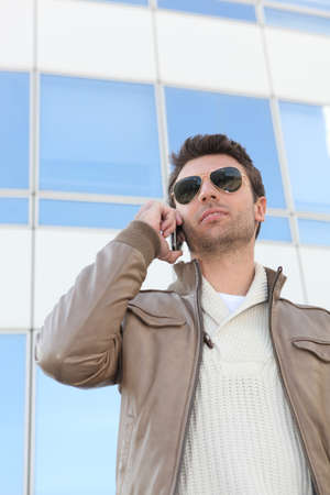 Urban man in aviators with a mobile phone Stock Photo - 11947693