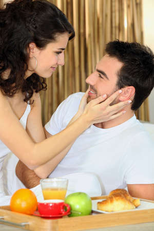 Couple eating breakfast in bed photo