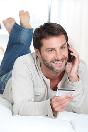 Smiling man using a credit card to pay for a purchase by phone photo