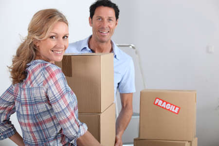 over the shoulder view: Couple moving boxes Stock Photo