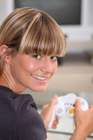 captivated: Young woman playing a video game Stock Photo