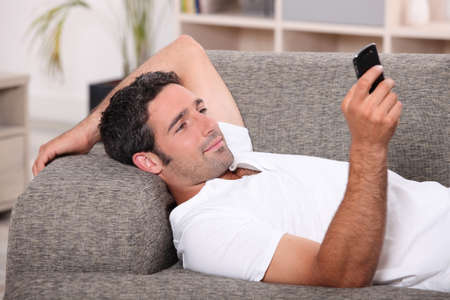 lying on couch: Amused man lying on the sofa sending a text message