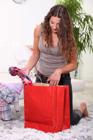 kneeling woman: portrait of a woman with shopping bag