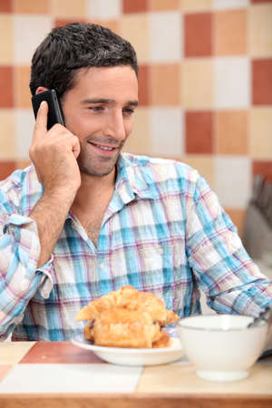 Man taking a call at breakfast photo