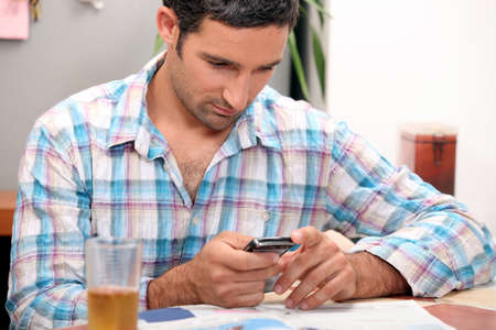 Man reading magazine and sending text message Stock Photo - 11947197