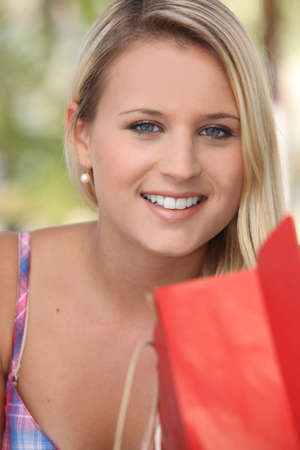 Smiling young woman with a store bag photo
