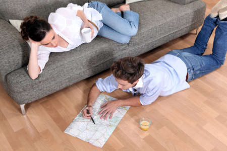 lying on floor: a couple looking a map at home Stock Photo