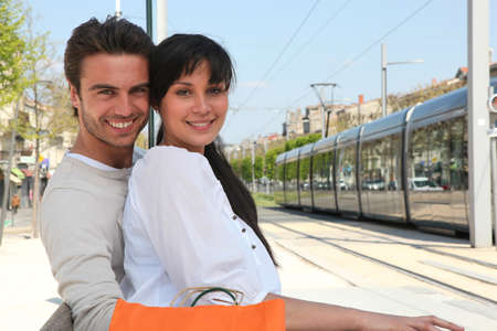 hugging knees: Couple waiting for tram Stock Photo