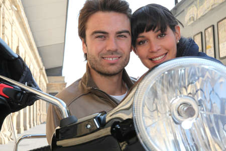 Young couple smiling on a motorbike photo