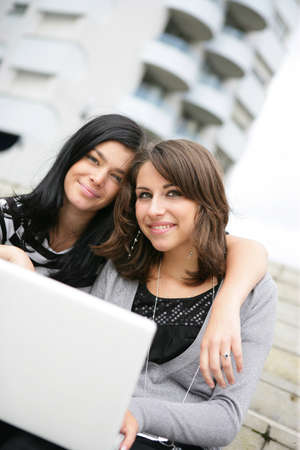 Two students using laptop on campus photo