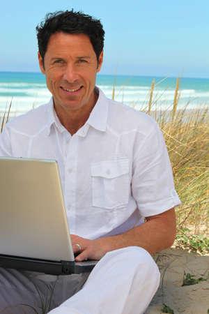 man 40 50: Man happy working on the beach.