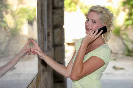 enquiring: Blond woman outside restaurant using mobile telephone Stock Photo