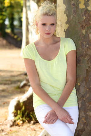 fair skinned: Young woman standing by a plane tree Stock Photo
