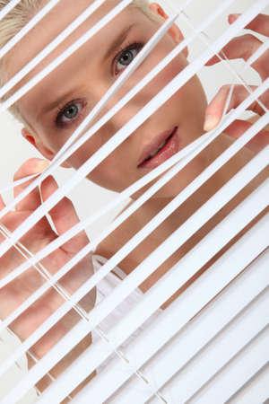fair skinned: Woman peering through some blinds