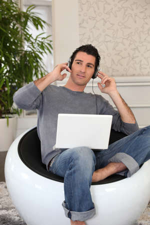 Relaxed man listening to music on laptop photo