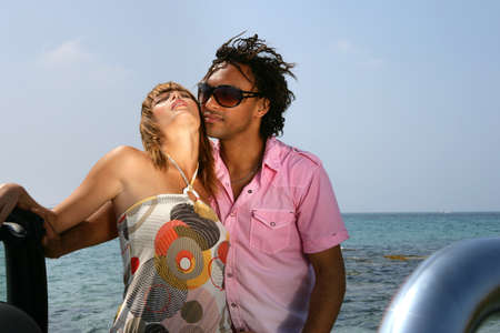 modifiable: Couple stood by convertible at the beach Stock Photo
